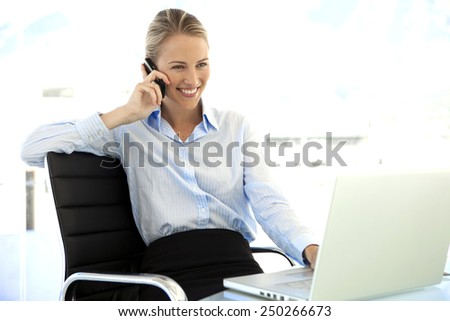 Pretty businesswoman on the phone at workplace - stock photo