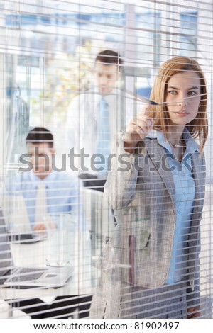 Pretty businesswoman peeping through blind nosily, colleagues working in background.? - stock photo