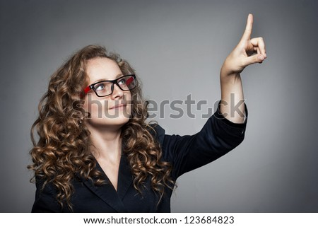 Pretty Businesswoman pointing her finger on empty copy space - stock photo