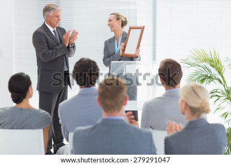 Pretty businesswoman receiving prize in meeting room - stock photo