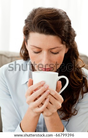 Pretty businesswoman smelling her coffee sitting on the sofa at home - stock photo