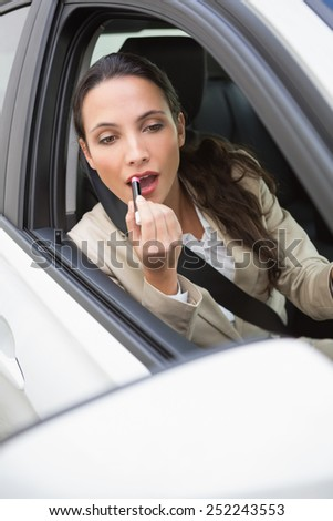 Pretty businesswoman using wing mirror to put on lipstick in her car - stock photo