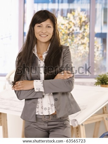 Pretty businesswoman with long hair standing in office with arms crossed, looking at camera, smiling.? - stock photo