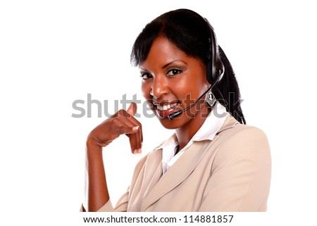 Pretty call center employee smiling at you while wearing her headset against white background - stock photo