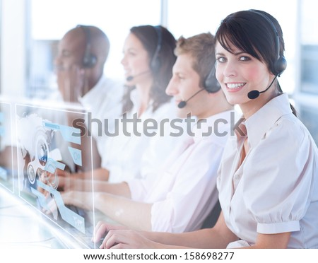 Pretty call center worker using futuristic holographic interface smiling at camera in office - stock photo