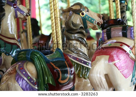 Pretty carousel horses on the merry-go-round at the amusement park - stock photo