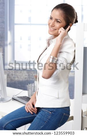 Pretty casual business woman sitting on office desk in jeans, talking on mobile phone, smiling. - stock photo