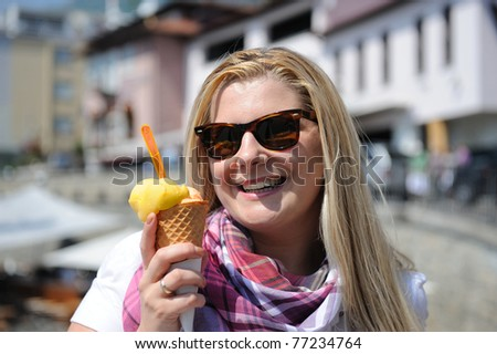 Pretty casual summer girl eating ice cream outdoors - stock photo