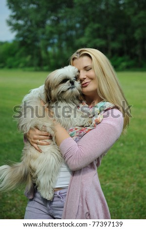 Pretty casual woman with cute little shih tzu dog outdoors in a park - stock photo