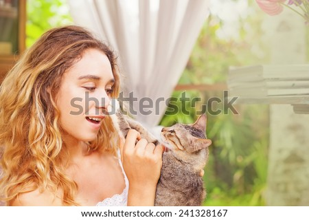 pretty cat owner putting cat's paw on her nose - stock photo