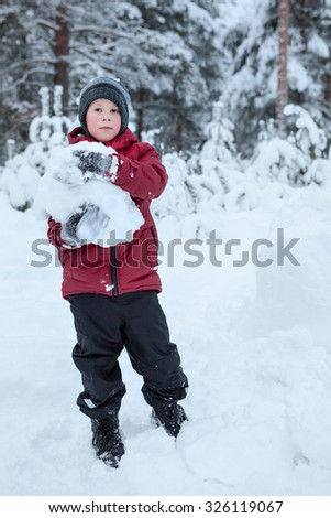 Pretty Caucasian boy holding snowball while playing and making snowman on snow field - stock photo