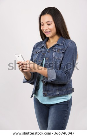 pretty caucasian casual teen with cellphone on grey background - stock photo