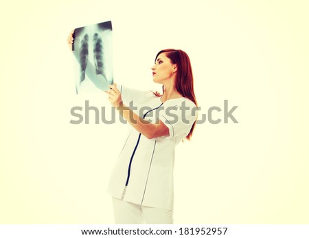 Pretty caucasian female doctor looking at x-ray. Isolated in white background - stock photo