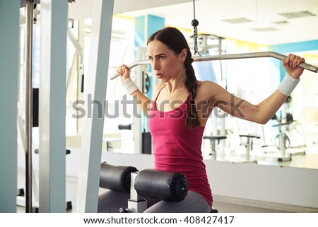 Pretty Caucasian girl in sportswear is working out pull-down machine in gym - stock photo