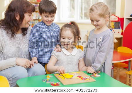 Pretty caucasian girl, kindergarten pupil, collect puzzle in the classroom at the green table. The teacher and two children watching and smiling. Horizontal color image - stock photo
