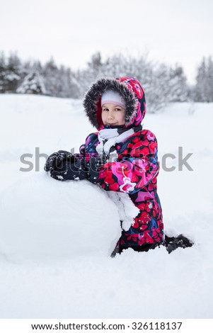 Pretty Caucasian girl playing with snowball while making snowman at winter field - stock photo