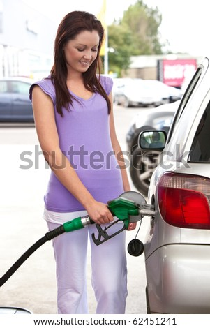 Pretty caucasian woman refueling her car in a service station - stock photo
