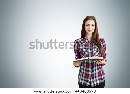 Pretty caucasian woman with open book on light grey background with copyspace. Education concept - stock photo