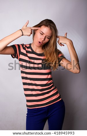 Pretty caucasian young blonde woman student posing in the studio isolated on white background. She folded her hands in the form of a gun.  shoots herself in the head - stock photo