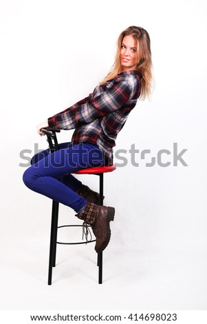 pretty charming girl Caucasian blonde in a plaid shirt and blue pants sitting on a bar stool,  leaned to the right, isolated on white - stock photo