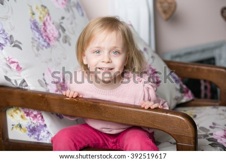 Pretty cheerful cheerful little girl sits in a bright room in a vintage chair and smiling - stock photo