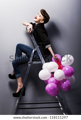 Pretty cheerful fashion retro model teen girl laughing on ladder in studio with balloons - stock photo