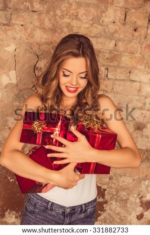 Pretty cheerful girl holding birthday presents - stock photo