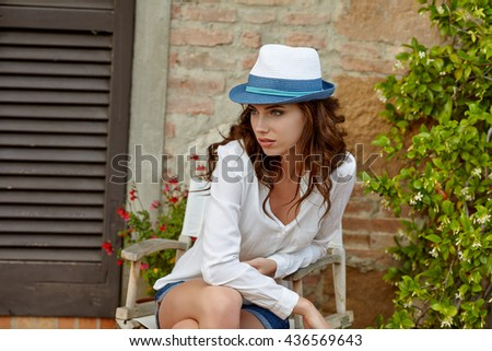Pretty cheerful woman in the Tuscany garden - stock photo