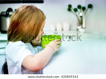 Pretty child girl five years old drinking woter from glass under the supervision of a beautiful young woman - stock photo
