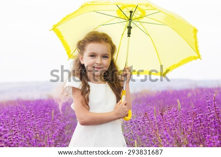 Pretty child girl is in a purple lavender field holds an yellow umbrella  - stock photo