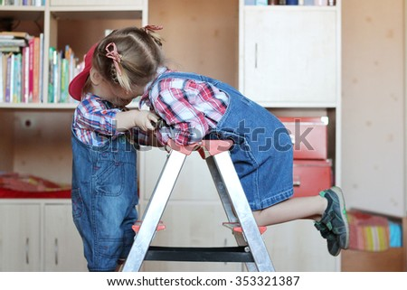 Pretty child girl whispering something to her little toddler brother, both wearing in jeans overalls and standing on the step ladder, indoor building concept - stock photo