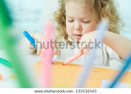 Pretty child having fun drawing at kindergarten - stock photo