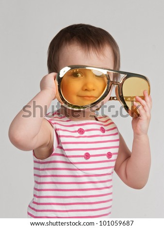 Pretty child with giant yellow sunglasses - stock photo