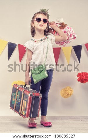 Pretty child with the suitcase and heart shaped glasess looking for the vacation. - stock photo
