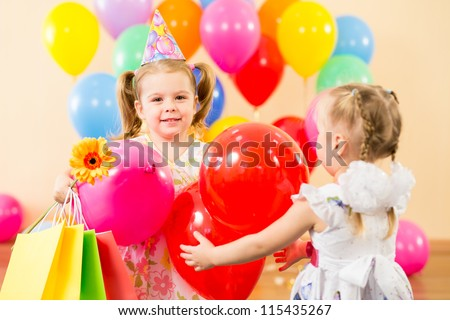 pretty children with colorful balloons and gifts on birthday party - stock photo