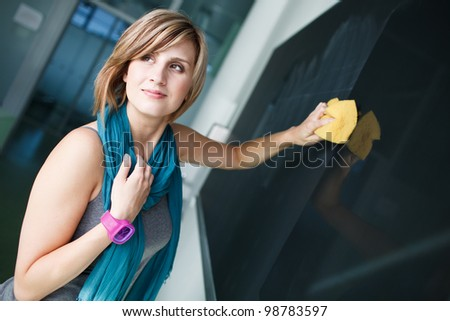 pretty college student/young teacher erasing the chalkboard/blackboard during a math class (color toned image; shallow DOF) - stock photo