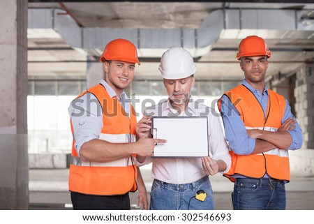 Pretty construction team is ready to sign a contract. The old architect is showing a folder of document. The young worker is pointing his finger at it. The men are smiling - stock photo