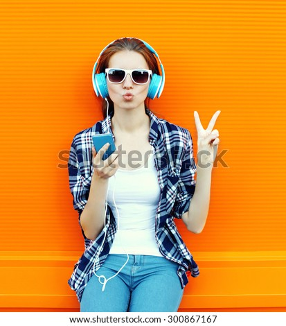 Pretty cool girl having fun and listens to music in the headphones on smartphone over colorful background - stock photo