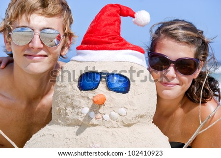 Pretty couple having fun at beach with perfectly build christmas snowman made out of sand wearing sunglasses - stock photo