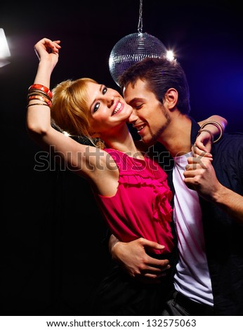 Pretty couple of young people dancing on a disco - stock photo