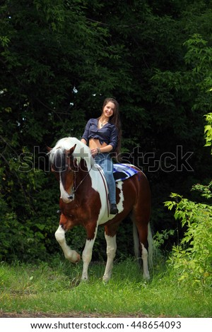 Pretty cowgirl bareback riding painted horse - stock photo