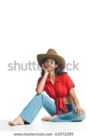 Pretty cowgirl seated on the ground. Isolated on white background. - stock photo