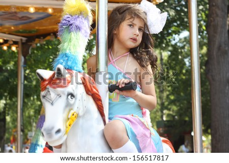 pretty cute little girl on the carousel - stock photo
