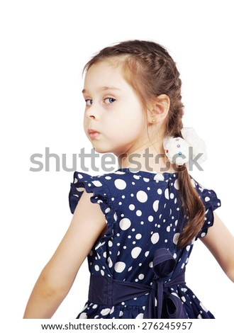 Pretty cute young girl wearing the dark blue dress looking back - stock photo
