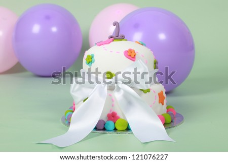 Pretty dainty white double tier round fondant plastic iced cake with green orange pink and blue hearts flowers and balls - stock photo