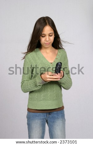 pretty dark hair preteen girl texting on her cell phone - stock photo