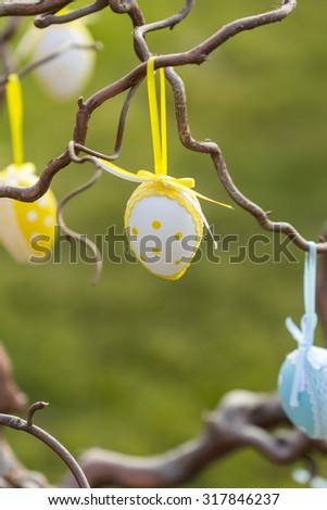 Pretty decorated yellow and blue polka dot Easter eggs hanging in a tree in a garden or park by colorful ribbons symbolic of a childhood egg hunt or party celebration - stock photo