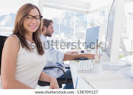 Pretty designer smiling at the camera as her colleague works behind her - stock photo