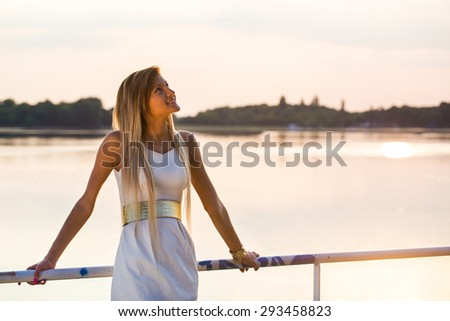 pretty dressed young girl looking up at a lake at sunset - stock photo