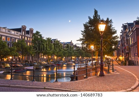 Pretty dutch doll houses illuminated and reflected along the tranquil canals of Amsterdam. - stock photo